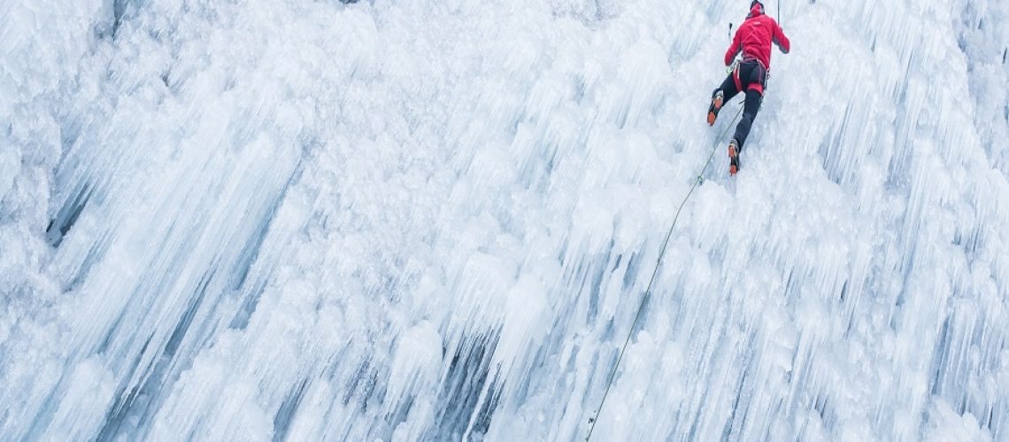 Ice climber ascending a frozen waterfall.